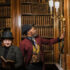 Two actors in victorian costume reading and looking at books in a library