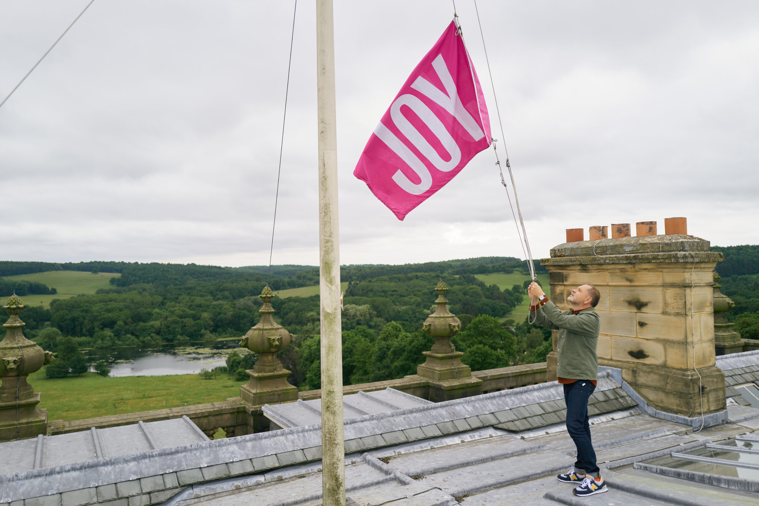 Anthony Burrill raising a flag on the roof of Harewood House